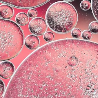 Abstraktes öl fällt mit luftblasen im wasser auf unscharfem hintergrund