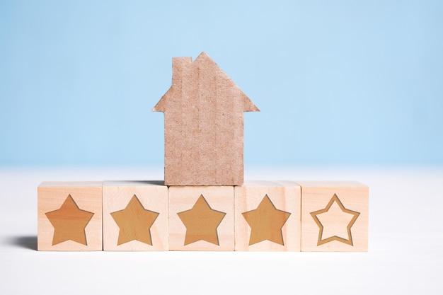 Abstraktes papphaus auf hölzernen würfeln mit sternen auf einem blau. wohnungsbewertung.