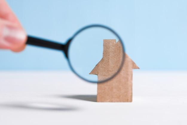 Abstraktes papphaus, hand hält ein glasvergrößerungsglas. überprüfung der wohnung, der rechtmäßigkeit der transaktion.
