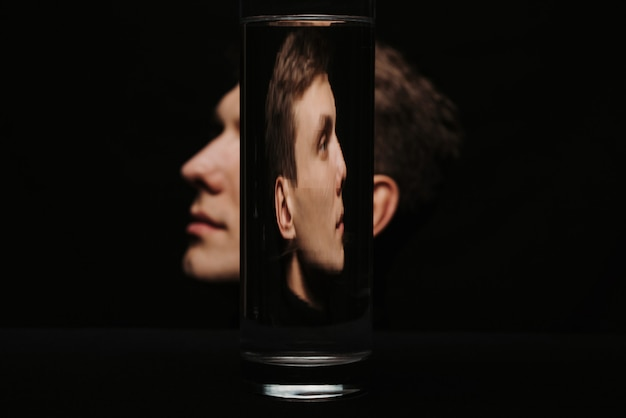 Abstraktes porträt eines mannes im profil durch einen behälter des wassers
