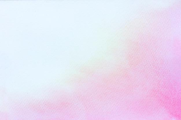 Abstraktes rosa aquarell auf weißem hintergrund. die farbe, die im papier spritzt. es ist eine gezeichnete hand.