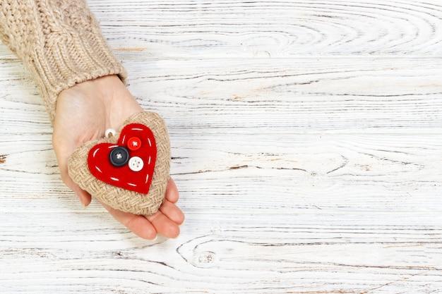 Abstraktes rotes herz, das in der hand für valentinstag strickt. weinlesebildton auf hölzernem bachground. liebeskonzept mit copyspace