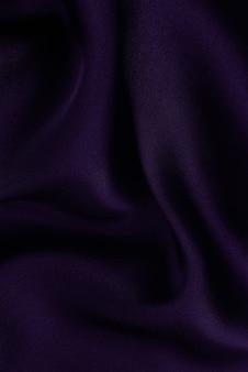 Abstraktes seidiges satintuch, stoff-textil-drapierung mit gewellten faltenfalten. mit weichen wellen, die im wind wehen. textur aus zerknittertem papier