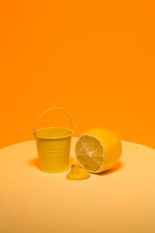 Abstraktes stillleben mit einem gelben eimer und einer zitrone auf einer orange