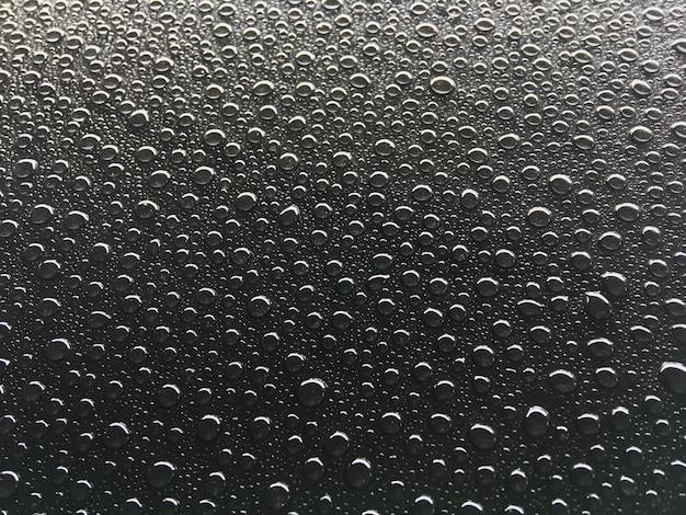 Abstraktes tröpfchenwasser fällt auf einen schwarzen hintergrund