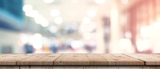 Abstraktes unscharfes bild des kaufhauses mit hölzernem tischzählerhintergrund für show
