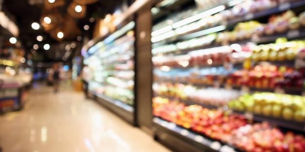 Abstraktes unscharfes organisches frisches obst und gemüse auf lebensmittelregalen im supermarktgeschäft defokussierten bokeh-lichthintergrund