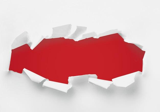 Abstraktes zerrissenes weißes papier auf rotem hintergrund