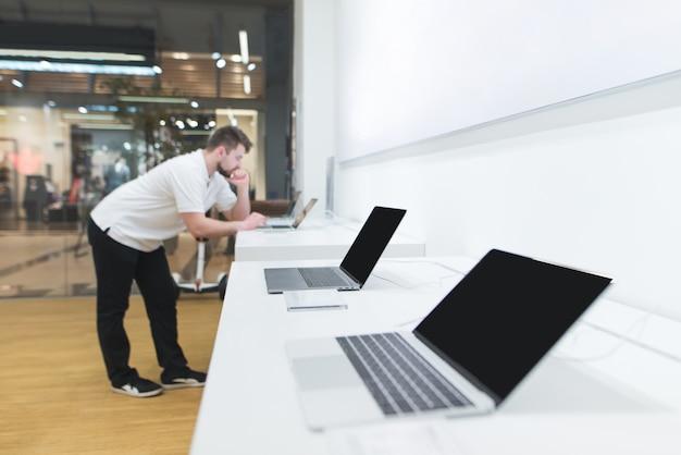 Abteilung für laptops im technologieladen. käufer wählt einen laptop im elektronikgeschäft.