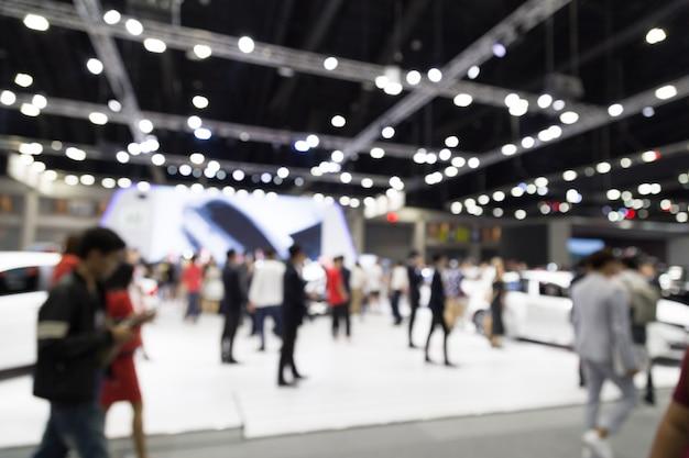Abtract-unschärfeleute im ausstellungshallenautoausstellungs-ereignishintergrund