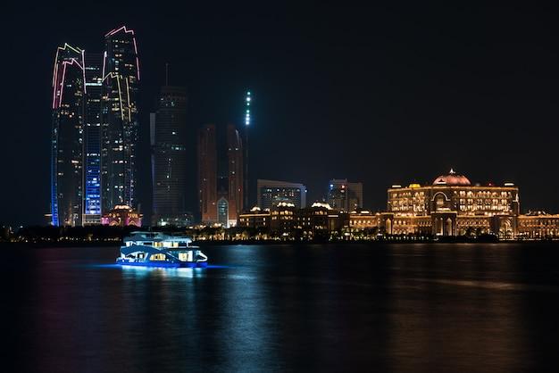 Abu dhabi gebäude skyline vom meer in der nacht