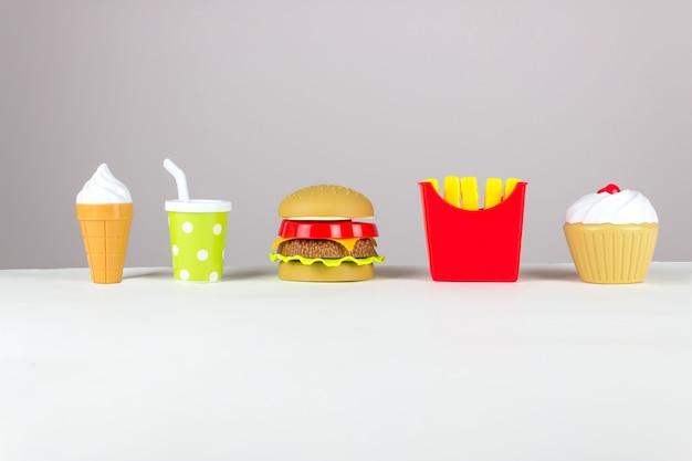 Abwechslungsreiches spielzeug fastfood in miniatur auf weißem hintergrund. konzept der schädlichen künstlichen nahrung.