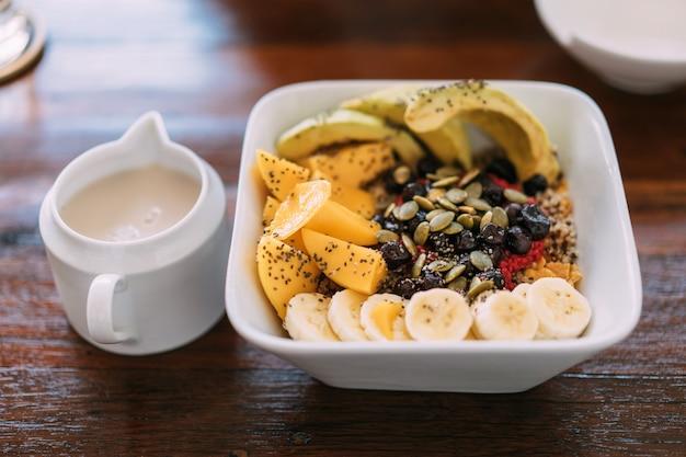 Acai bowl mix mit frischer mango, avocado, banane, beeren, sonnenblumenkernen, chiasamen und müsli.