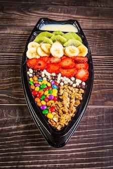 Acai gefroren mit banane, kiwi, müsli und süßigkeiten zum teilen.