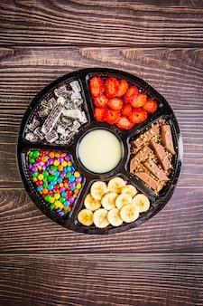 Acai gefroren mit banane, müsli, schokolade und süßigkeiten zum teilen.