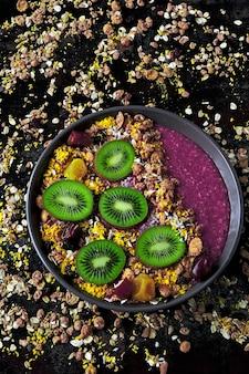 Acai schüssel mit müsli und kiwi auf dem hintergrund von verstreutem müsli.