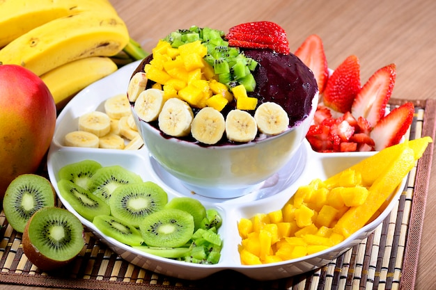 Acai-schüssel mit obstsalat-bananen-mango-kiwi und erdbeere