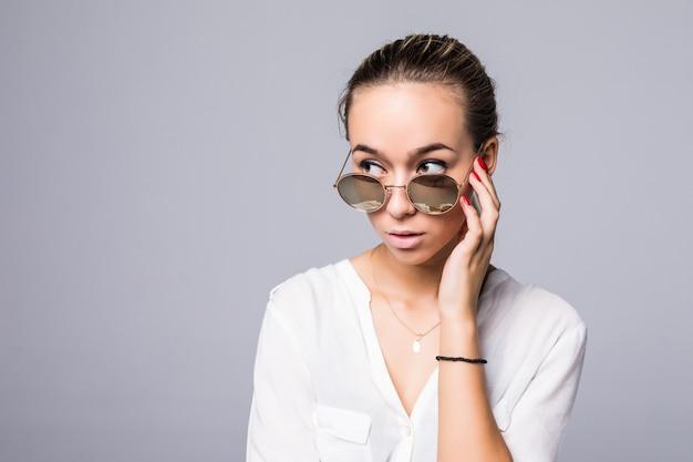 Accessoires, brillen, mode, menschen und luxuskonzept - schöne junge frau in eleganter schwarzer sonnenbrille über grauer wand