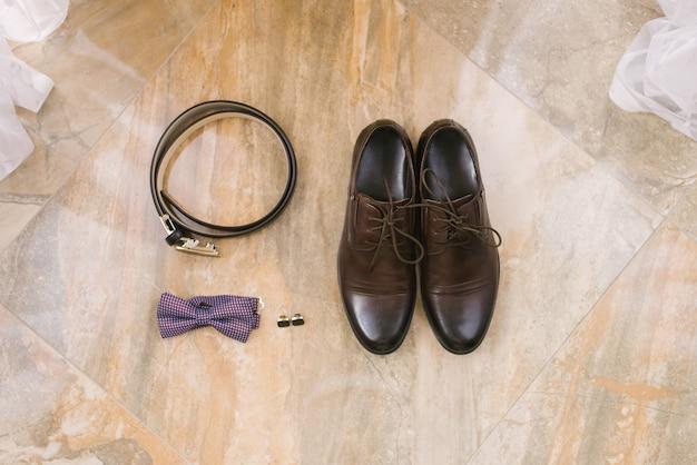 Accessoires für den bräutigam: braune schuhe mit schnürsenkeln, manschettenknöpfen, gürtel und lila fliege auf beige