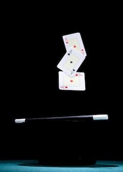 Aces, die karte über dem schwarzen zylinder und dem zauberstab gegen schwarzen hintergrund ausüben