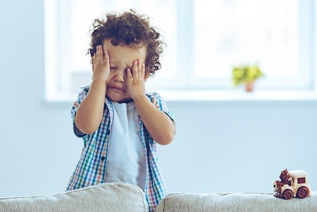 Ach nein! kleiner afrikanischer junge weint und reibt sich die augen, während er zu hause auf der couch steht