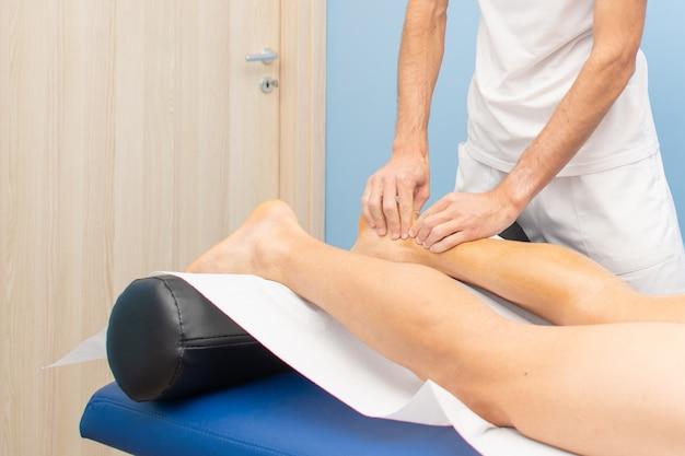Achillessehne. die hände eines physiotherapeuten während einer behandlung