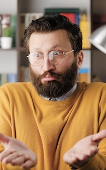 Achselzucken, ich weiß es nicht. verwirrter bärtiger mann mit brille im büro oder apartmentzimmer, der in die kamera schaut und emotional seine schultern drückt und seine hände ausbreitet, um seine unwissenheit zu zeigen. nahaufnahme