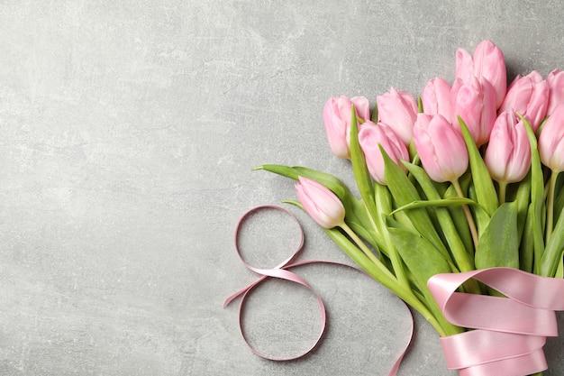 Acht aus band und tulpen auf grauem hintergrund, platz für text