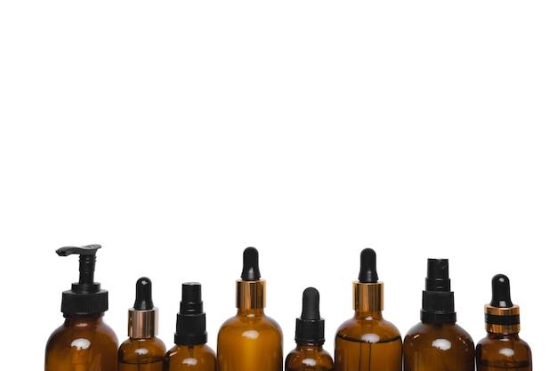 Acht braune glasflaschen mit pipetten auf weißem hintergrund