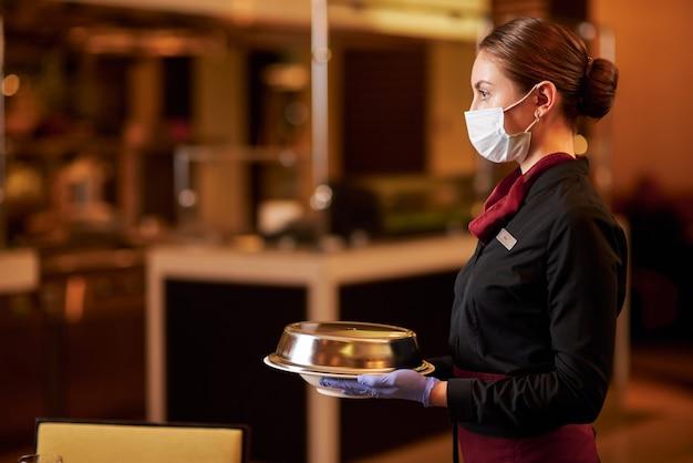 Achtsame kellnerin, die beim servieren von speisen gesichtsmaske trägt