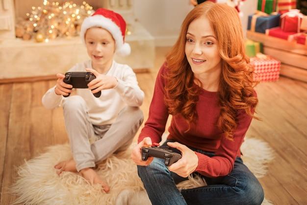 Achtsame reife dame, die auf dem teppich sitzt und aufgeregt einen fernsehbildschirm betrachtet, während sie spaß und videospiele mit ihrem kind hat.