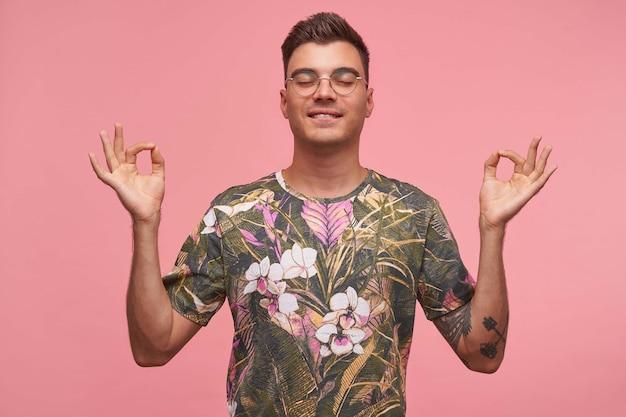 Achtsamer friedlicher hübscher mann, der drinnen meditiert, hände in der mudra-geste mit geschlossenen augen hält, finger im yoga-zeichen hält, isoliert