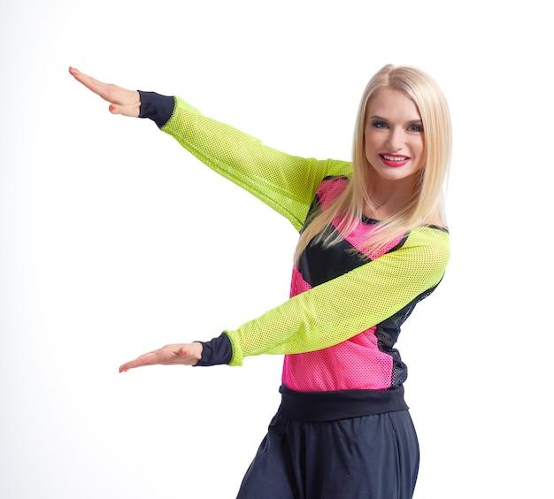 Achtung hier abgeschnittenes studioporträt einer attraktiven rotlippigen frau in sportbekleidung, die kopien an der seite in ihren händen hält und glücklich isoliert lächelt