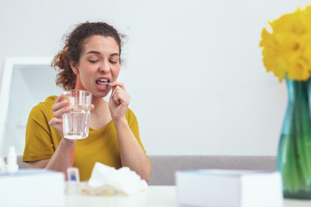 Achtung. junge mädchenpatientin, die vorsichtig schaut, während sie pillen nimmt, während sie angst hat, übermediziert zu werden