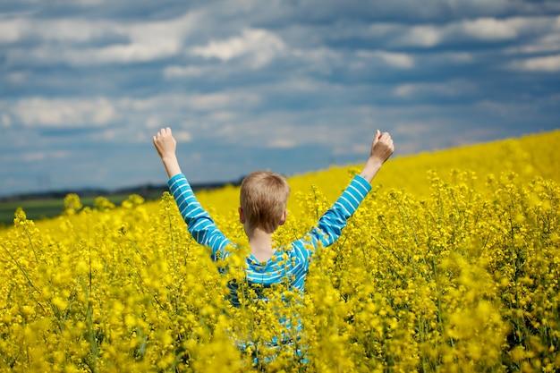 Ack-ansicht glücklicher lächelnder junge, der für freude auf einem gelben feld springt