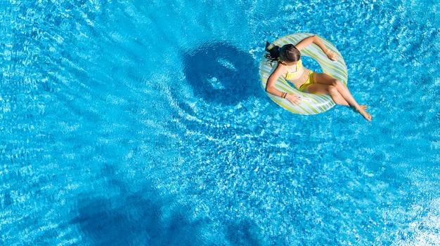 Acrive mädchen in der luftaufnahme des schwimmbades von oben, kind schwimmt auf aufblasbarem ringkrapfen, kind hat spaß im blauen wasser auf familienferienort