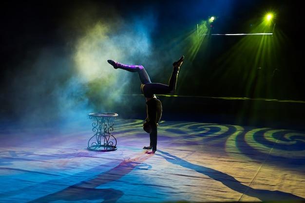 Acrobat führt einen schwierigen trick im zirkus aus.