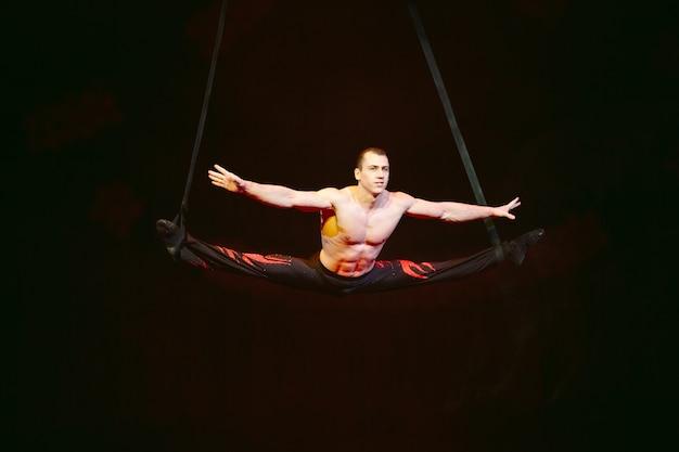 Acrobat führt im zirkus einen schwierigen trick aus.
