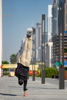 Acrobat hält mit dem verschwommenen stadtbild von dubai das gleichgewicht in den händen