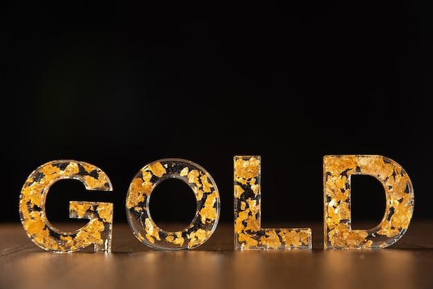 Acrylbuchstaben mit goldenen blättern, die das wort gold auf holzoberfläche auf schwarz bilden