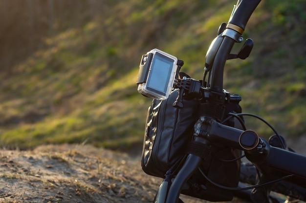 Action-kamera auf einem fahrrad mit einer fahrradverpackungstasche in einem wasserdichten gehäuse vor dem hintergrund der natur.