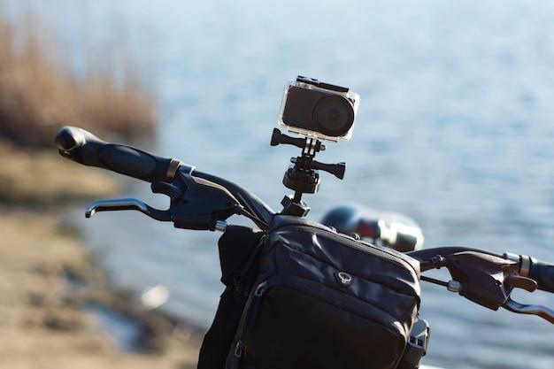 Action-kamera auf einem fahrrad mit einer fahrradverpackungstasche in einem wasserdichten gehäuse vor dem hintergrund des flusses.
