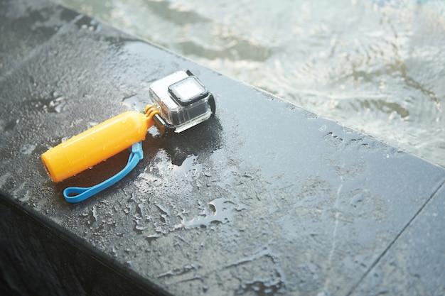 Action-kamera in wasserdichtem gehäuse und schwimmendem handgriff an der poolseite