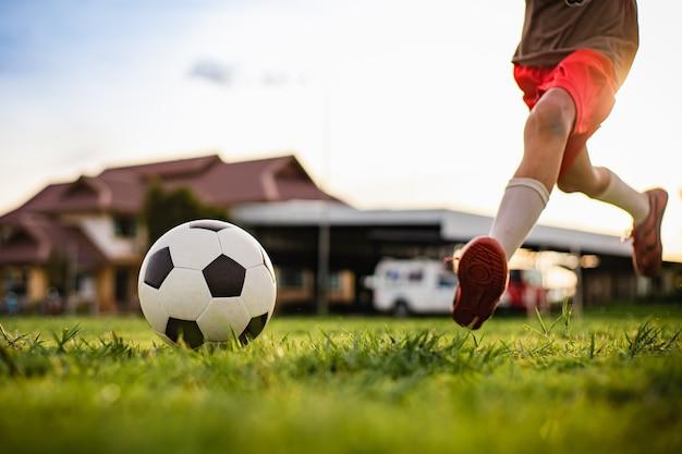 Action-sport im freien von jungen, die spaß haben, fußballfußball für übung zu spielen.