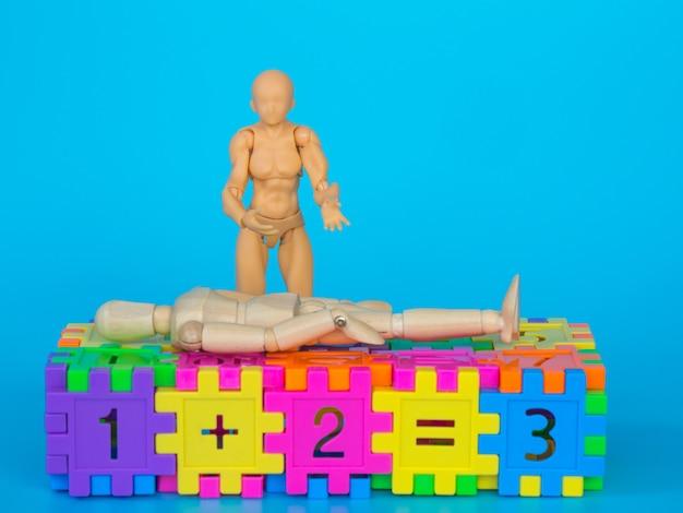 Actionfigur, die in bunten plastikzahlen steht und ein kopfschmerzschauspiel macht