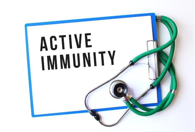 Active immunity-text auf medizinischem ordner mit dokumenten und stethoskop auf weißem hintergrund. medizinisches konzept.