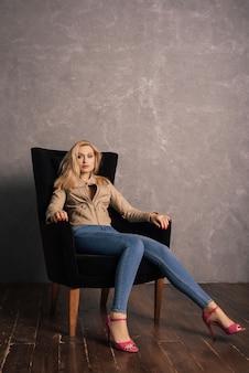 Adalt dame in jeans und lederjacke sitzt auf dem sessel und ruht sich aus