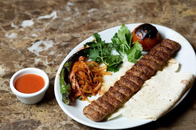 Adana kebab serviert mit fladenbrot, gegrilltem pfeffer und tomaten und karamellisierten zwiebeln
