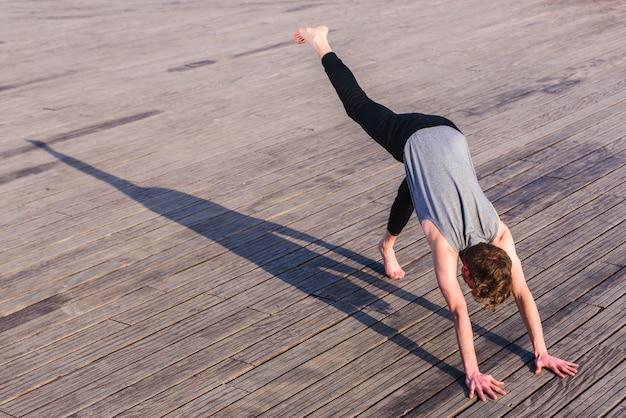 Adho mukha svanasana wurde von einem jungen outdoor-yoga-enthusiasten in der stadt praktiziert.