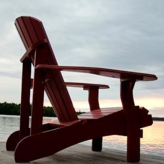 Adirondack stuhl auf einem pier am see, lake of the woods, ontario, kanada